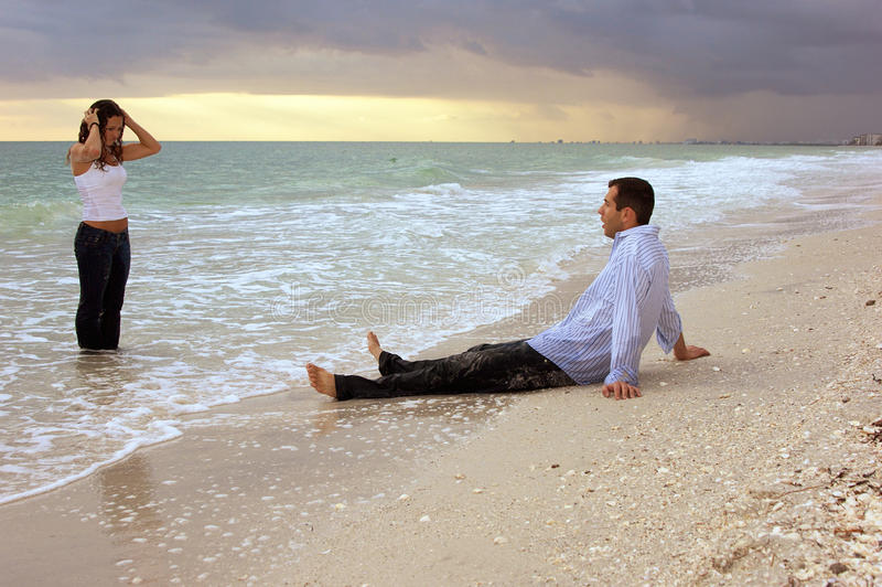 Mulher ideal que sai do oceano na frente do homem sobre imagem de stock royalty free