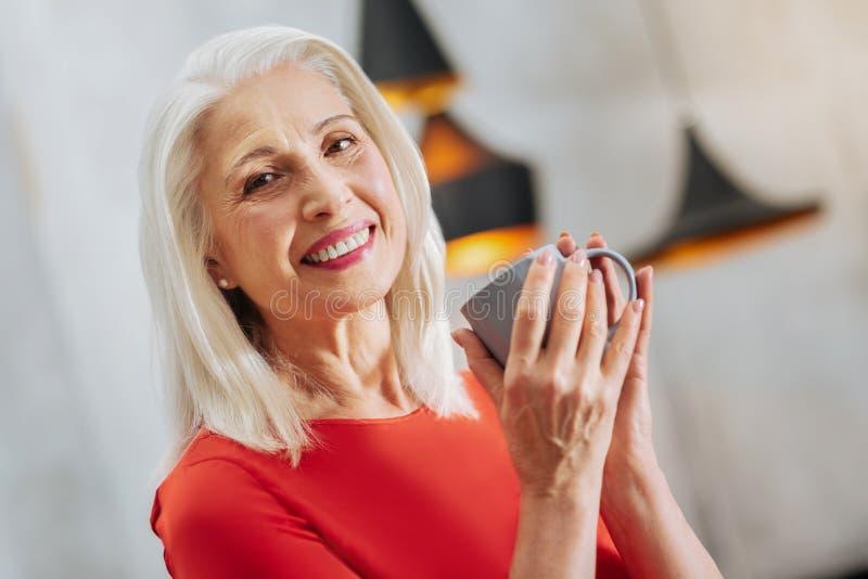 Mulher idosa agradável que guarda um copo fotografia de stock