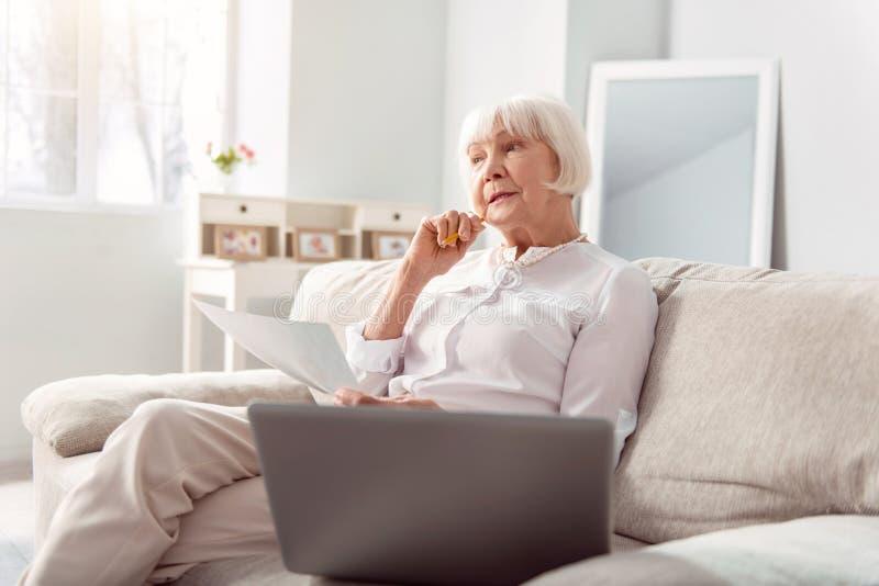 Mulher idosa agradável que pensa sobre melhorias do projeto foto de stock