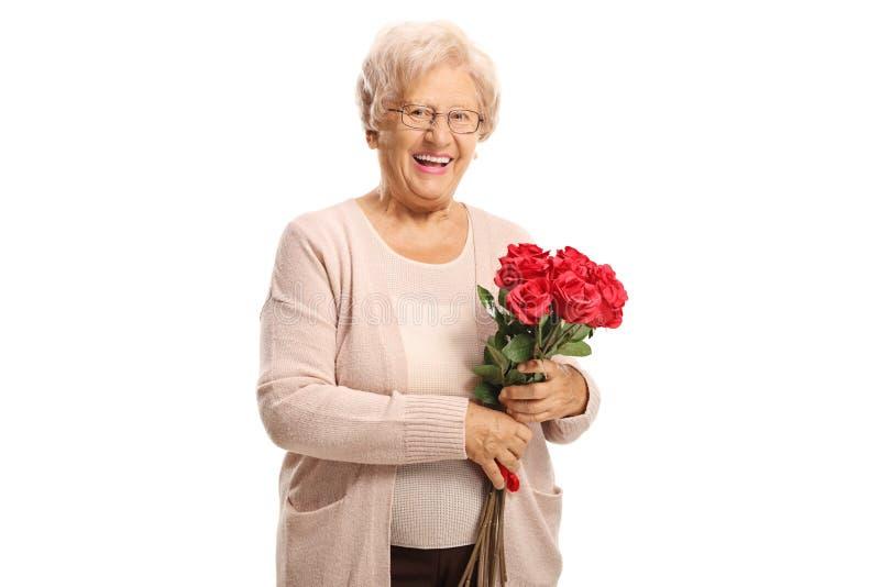 Mulher idosa alegre que guarda um ramalhete de rosas vermelhas e que sorri na câmera fotos de stock