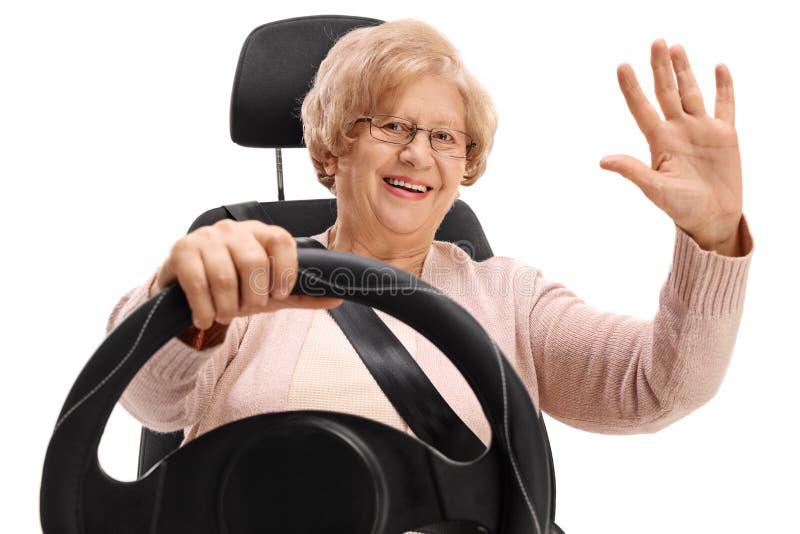 Mulher idosa alegre que senta-se em um banco de carro e em uma ondulação imagens de stock royalty free
