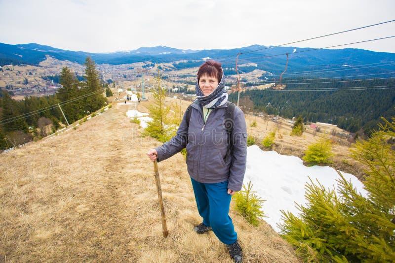 Mulher idosa 60 anos de caminhada velha nas montanhas com a neve que admira a vista bonita foto de stock