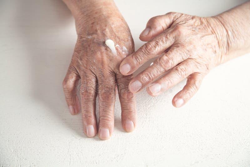 A mulher idosa aplica o creme na mão fotos de stock