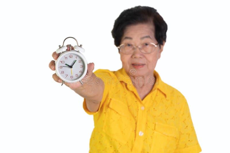 Mulher idosa asiática que guarda um despertador branco no fundo isolado A sociedade de envelhecimento do conceito que precisa o t imagem de stock