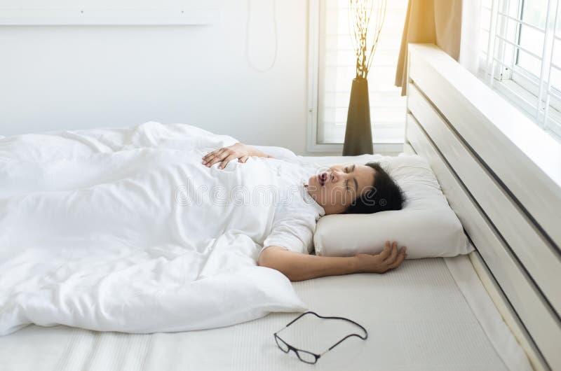 Mulher idosa asiática que ressona porque devido a cansado do trabalho, snor fêmea ao dormir na cama fotografia de stock