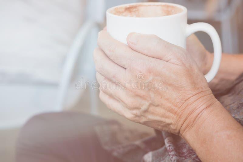mulher idosa asiática que senta-se e que descansa na cafetaria do café com imagem de stock royalty free
