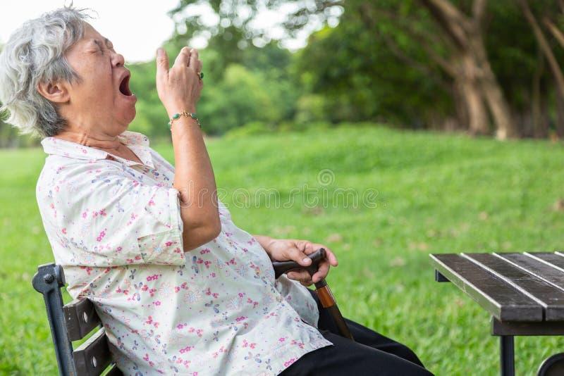Mulher idosa asiática tem expressão sonolenta, mulher idosa bocejando a boca aberta com a mão, idosos se sentindo bocejados, de fotografia de stock