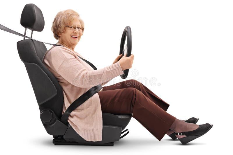 Mulher idosa assentada no banco de carro que guarda o volante foto de stock royalty free