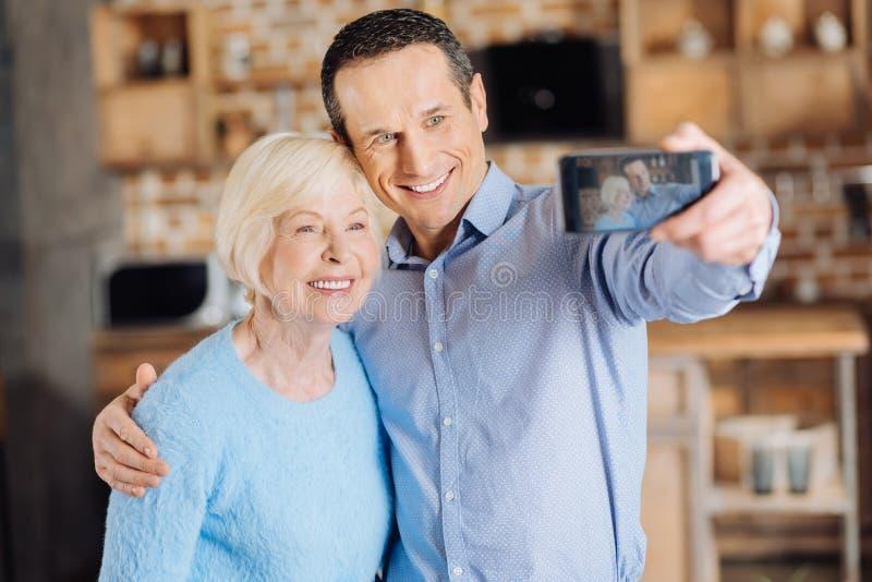 Mulher idosa bonita e seu filho que tomam selfies na cozinha fotografia de stock