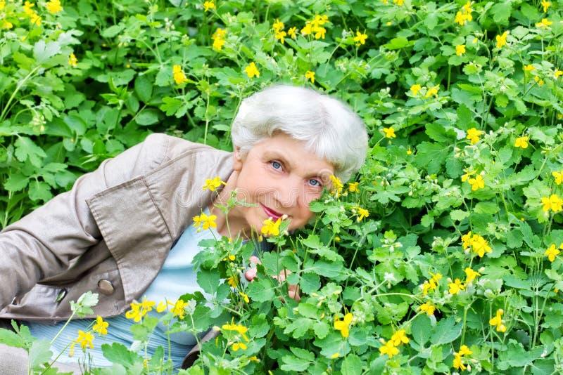 Mulher idosa bonita feliz que senta-se em uma clareira fotografia de stock