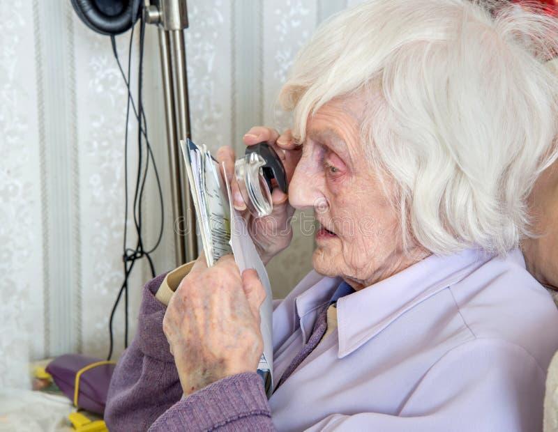 Mulher idosa cega com magnifyer imagem de stock