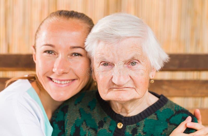 Mulher idosa com cuidador imagens de stock