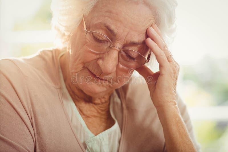 Mulher idosa com dor de cabeça imagens de stock