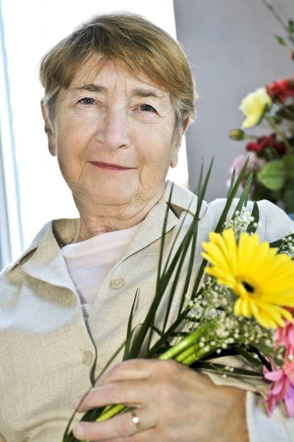 Mulher idosa com flores fotografia de stock