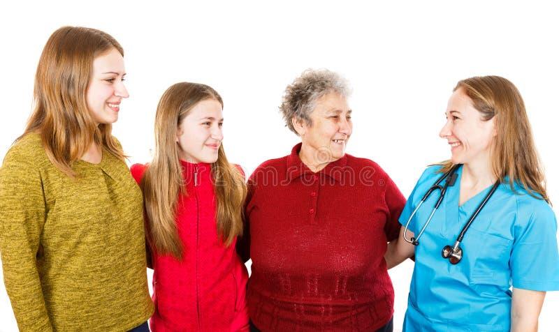 Mulher idosa com granddaugthers e doutor novo imagem de stock royalty free