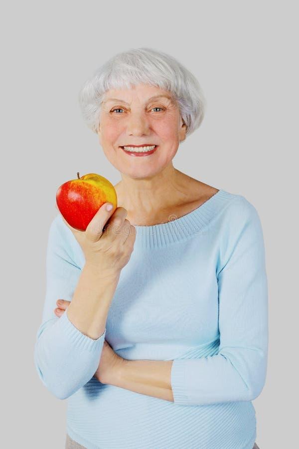 Mulher idosa com a maçã vermelha nas mãos em um fundo claro fotos de stock