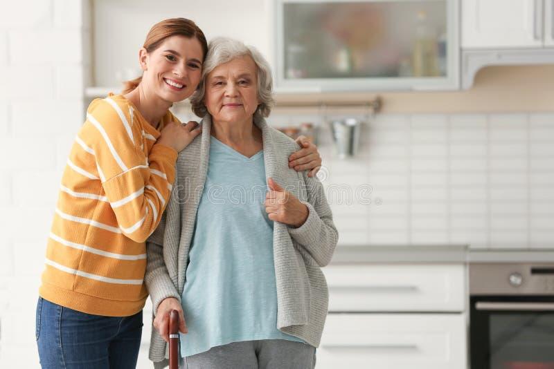 Mulher idosa com o cuidador fêmea na cozinha foto de stock