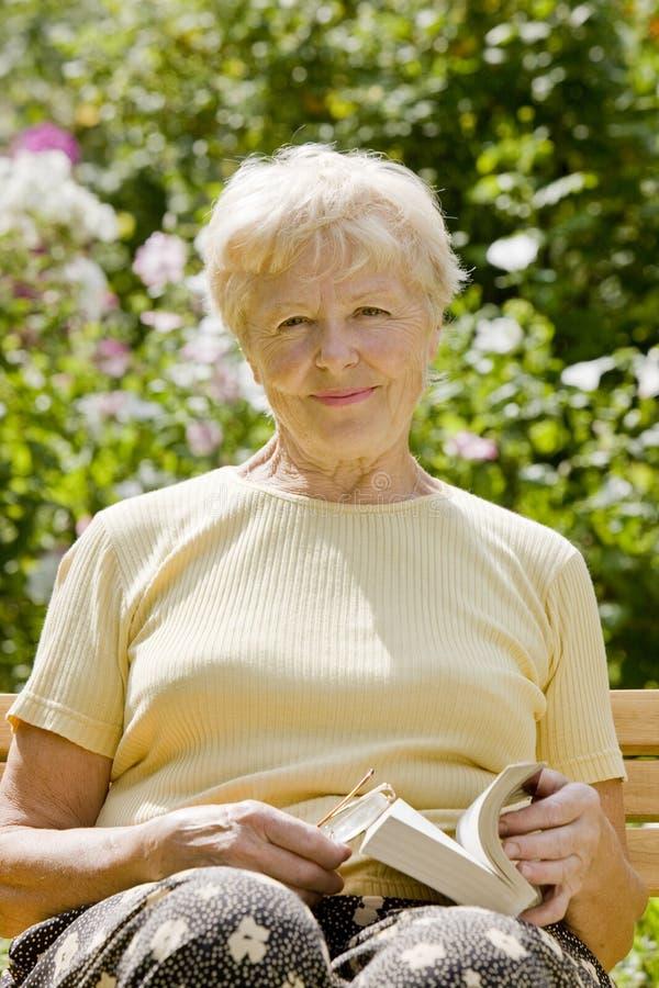 A mulher idosa com o livro fotografia de stock