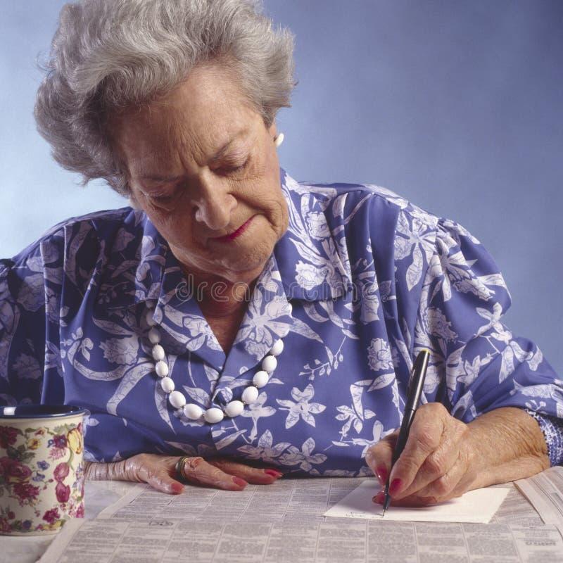 Mulher idosa com o section#1 classific jornal foto de stock royalty free