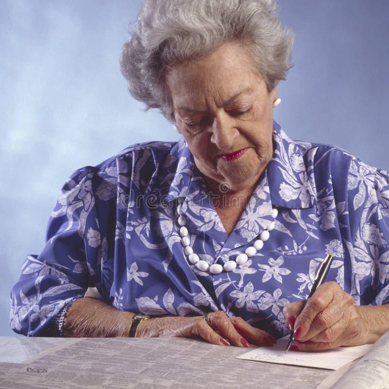 Mulher idosa com o section#2 classific jornal imagens de stock