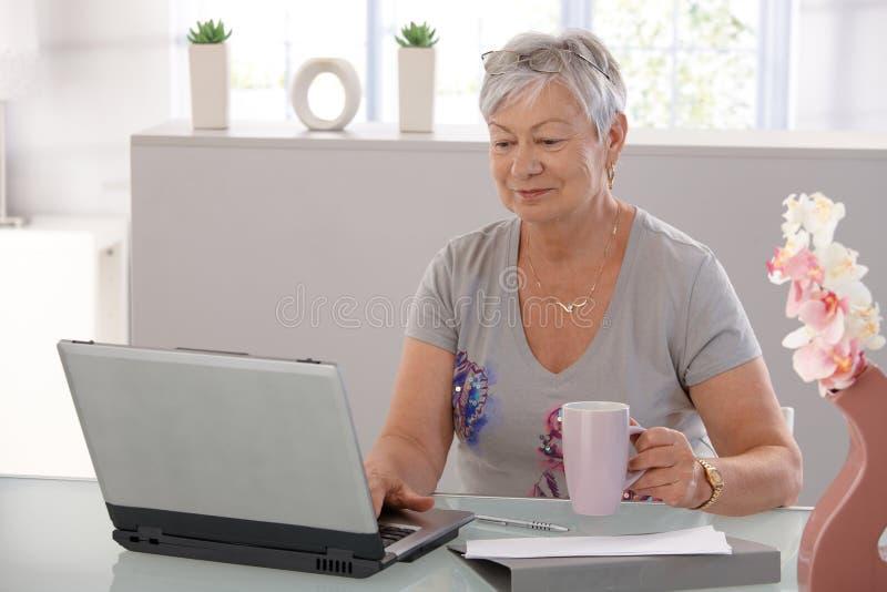 Mulher idosa com portátil foto de stock royalty free