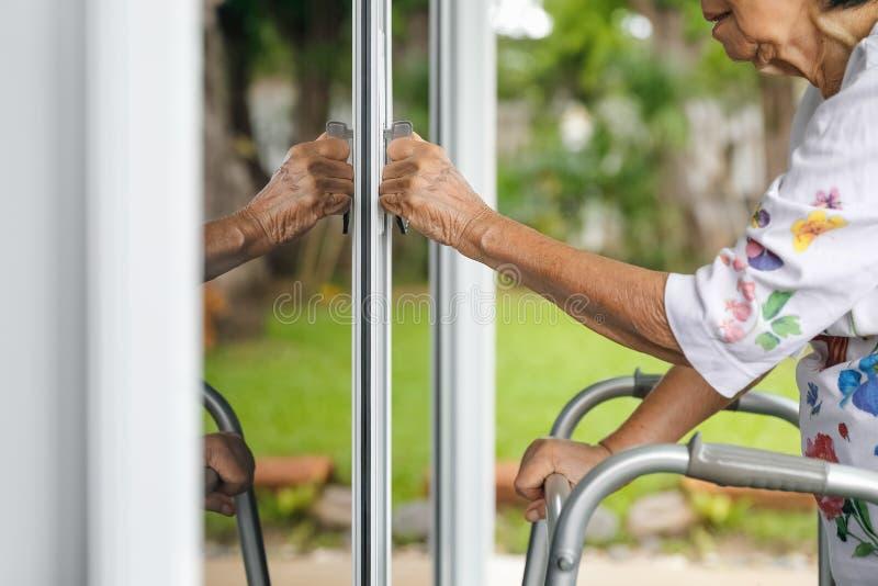 Mulher idosa com porta da rua de abertura chave imagem de stock
