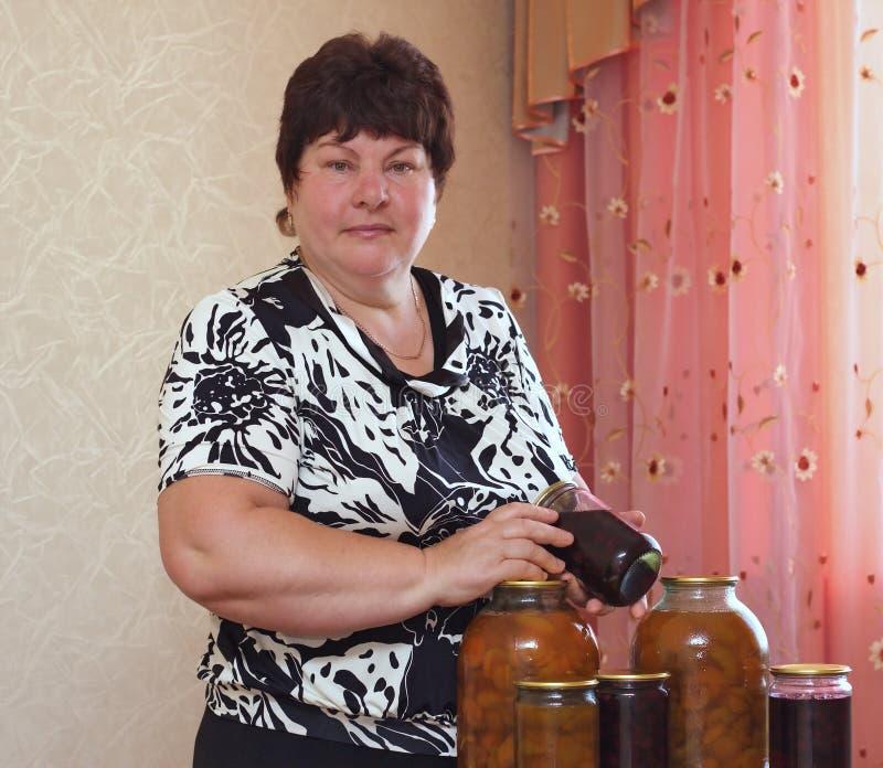 Mulher idosa com purveyances domésticos foto de stock royalty free
