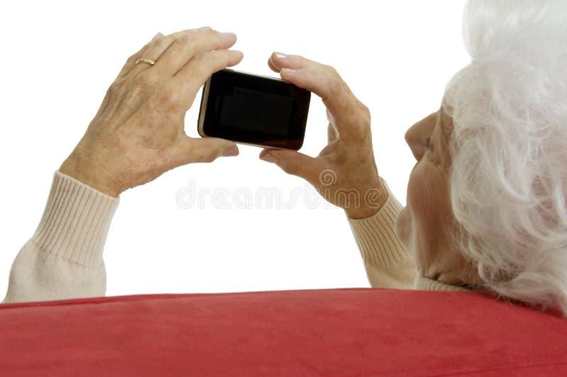 Mulher idosa com telefone esperto fotos de stock royalty free