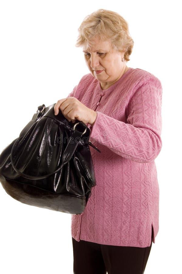 A mulher idosa com um saco preto foto de stock royalty free