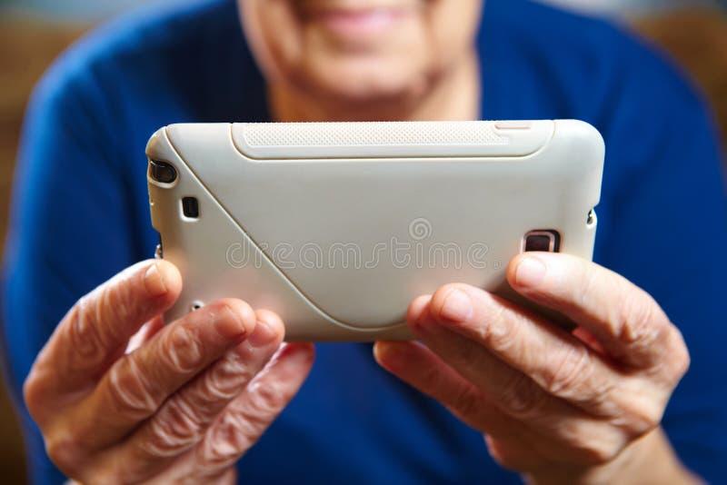 Mulher idosa com um smartphone imagens de stock royalty free