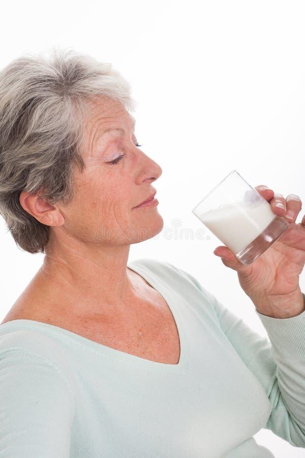 Mulher idosa com um vidro do leite foto de stock royalty free