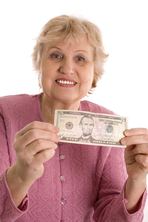 A mulher idosa com uma denominação de cinco dólares imagens de stock royalty free