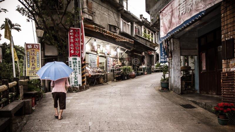 A mulher idosa da corcunda empurra-se acima de uma inclinação imagens de stock