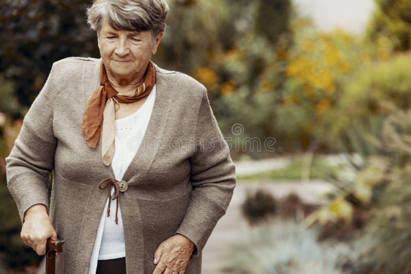 Mulher idosa de sorriso com a vara de passeio no meio da natureza fotos de stock royalty free