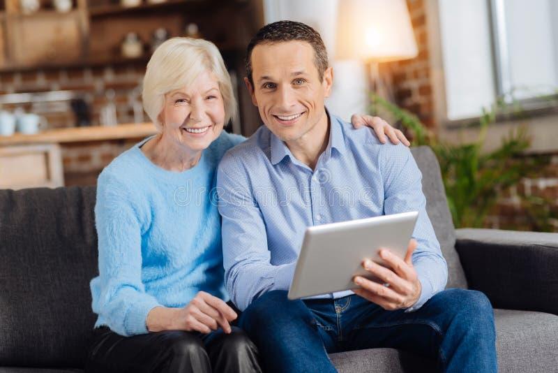 Mulher idosa de sorriso e seu filho que usa a tabuleta fotos de stock royalty free