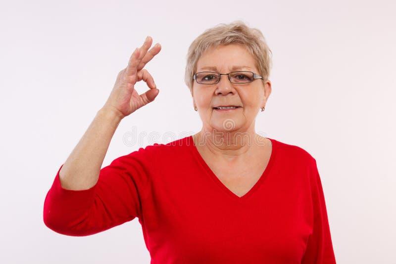 Mulher idosa de sorriso feliz que mostra o sinal aprovado, emoções positivas na idade avançada imagens de stock royalty free