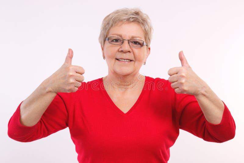 Mulher idosa de sorriso feliz que mostra os polegares acima, emoções positivas na idade avançada imagem de stock royalty free