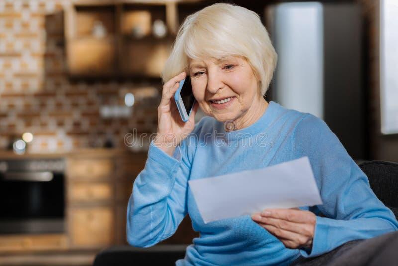 Mulher idosa deleitada que faz um telefonema fotografia de stock