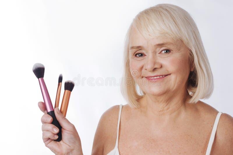 Mulher idosa deleitada que guarda ferramentas cosméticas fotografia de stock