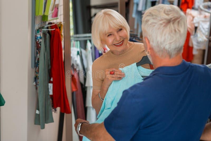 Mulher idosa deleitada que mostra um vestido a seu marido fotografia de stock