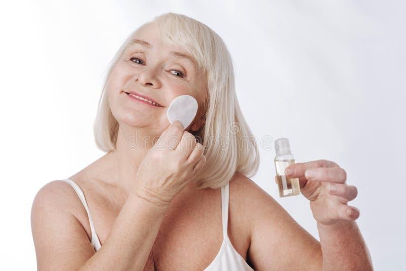 Mulher idosa deleitada que tem sua rotina diária dos cuidados com a pele fotos de stock