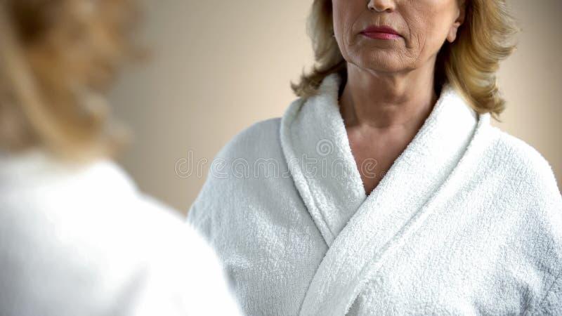Mulher idosa desagradada que olha seu pescoço na frente do espelho, processo de envelhecimento imagens de stock