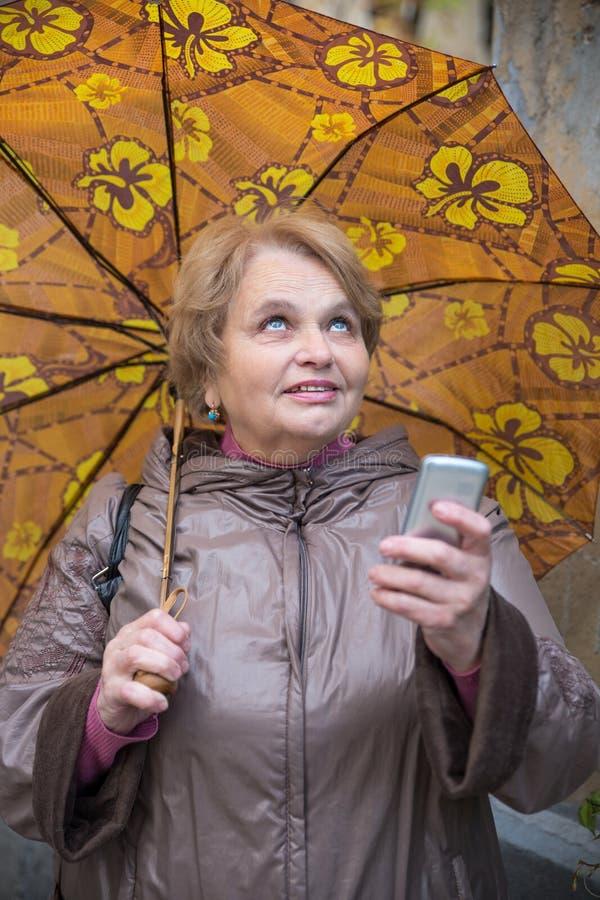 Mulher idosa do pensionista com guarda-chuva e telefone imagem de stock royalty free