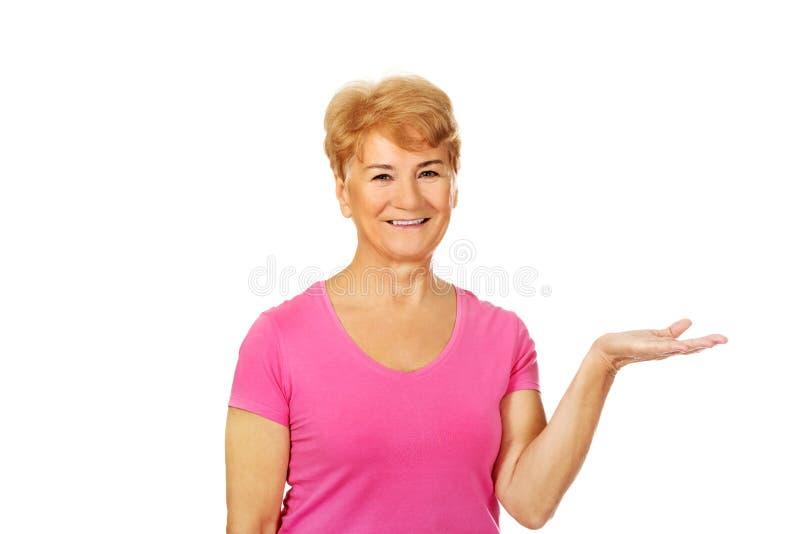 Mulher idosa do sorriso que apresenta algo na palma aberta fotografia de stock royalty free