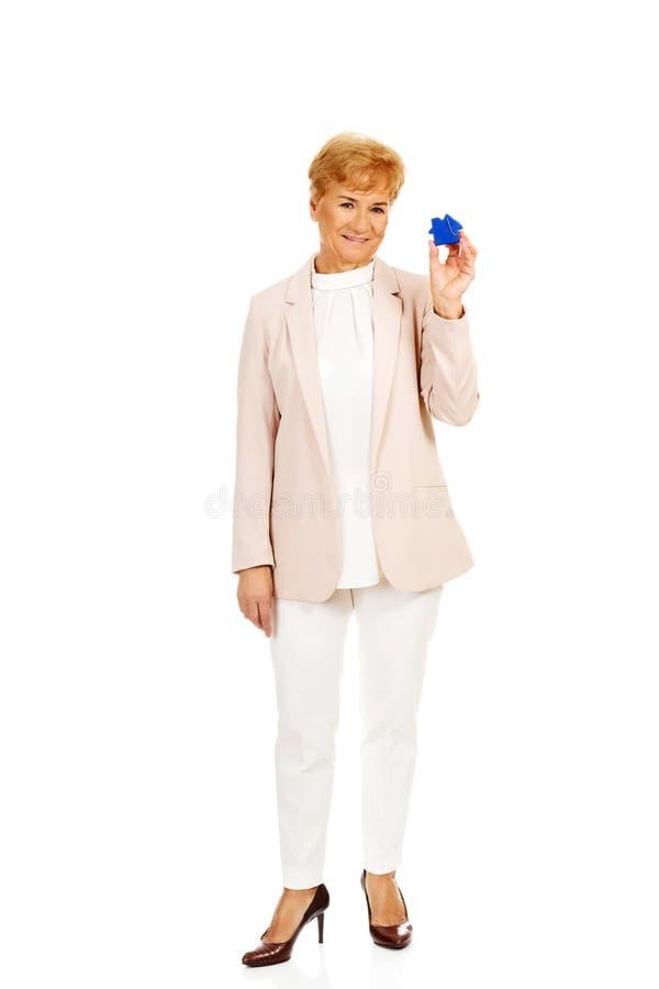 Mulher idosa do sorriso que guarda o pendente chave azul fotografia de stock royalty free