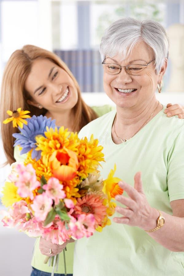 Mulher idosa e filha que sorriem feliz imagem de stock