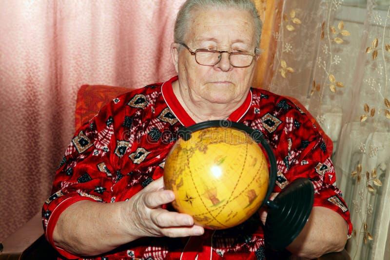 Mulher idosa e globo terrestre fotos de stock royalty free
