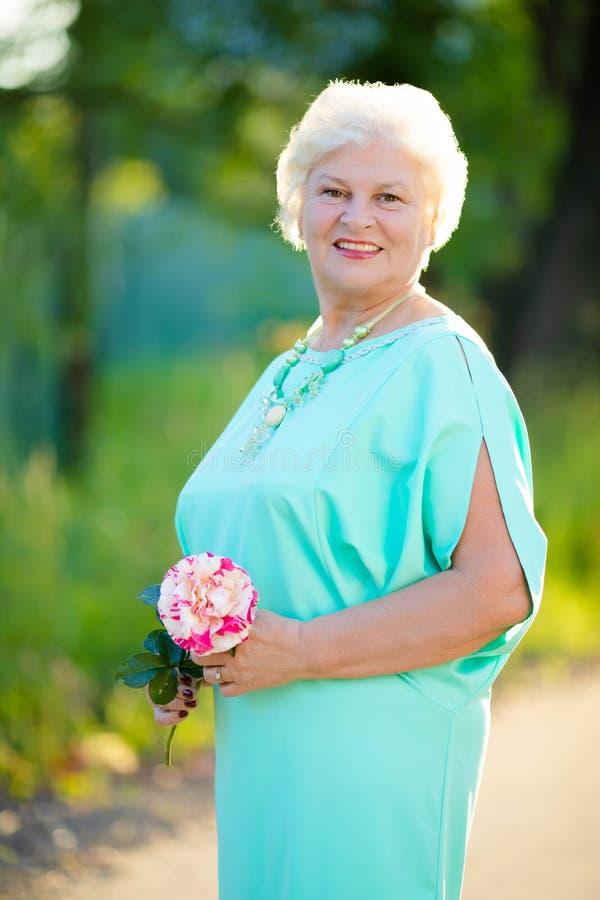 Mulher idosa elegante que sorri e que levanta com flor cor-de-rosa fora fotografia de stock royalty free