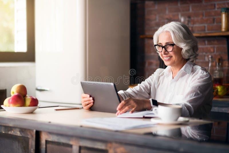 Mulher idosa elegante que usa o portátil foto de stock