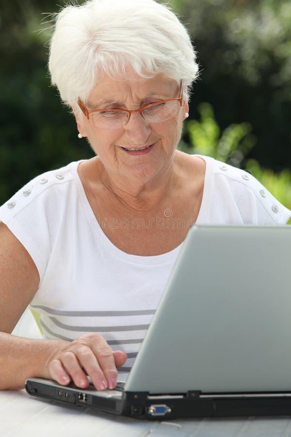 Mulher idosa em casa com computador foto de stock royalty free